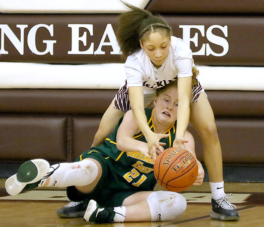 (Brad Davis/The Register-Herald) Woodrow Wilson's Keanti Thompson reaches to grab a loose ball away from Greenbrier East's Kate Perkins Saturday night in Beckley.