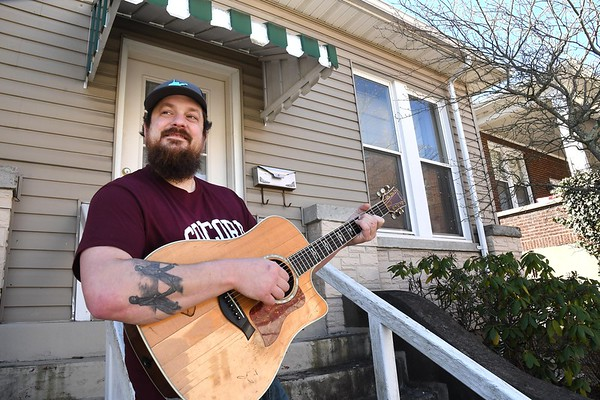 Matt Mullins, with the Bringdowns band, warms up before live streaming a song from his front porch on Prince Street in Beckley.<br /> (Rick Barbero/The Register-Herald)