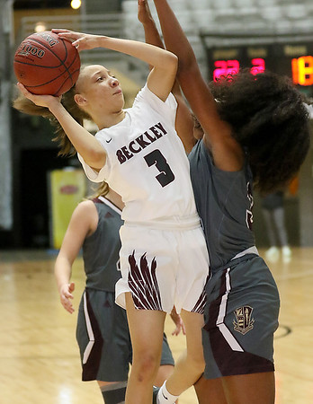 (Brad Davis/The Register-Herald) Woodrow Wilson's Keanti Thompson drives to the basket as George Washington's Nevaeh Harmon defends during the final night of Big Atlantic Classic action Saturday at the Beckley-Raleigh County Convention Center.