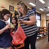 Kellie Laraba, right, with her two children, Loretta, left and Helena Laraba, received a free lunch that Sheets is offering to children at location on Neville Street in Beckley Thursday afternoon. They each received a turkey sandwish, chips and juice.<br /> (Rick Barbero/The Register-Herald)