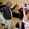 """(Brad Davis/The Register-Herald) Attendee Anna Johnston, right, dances in her seat with Tony Martin during the public mingling and moneymaking portion of the Hunks in Heels """"Fur"""" Real fundraising event Friday night at the Beckley Moose Lodge."""