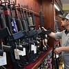 Benny Harper grabs a AR-15 to show a customer at Flat Top Arms in Beckley. Sales of ammo and guns have been on the rise due to the coronavirus. <br /> (Rick Barbero/The Register-Herald)