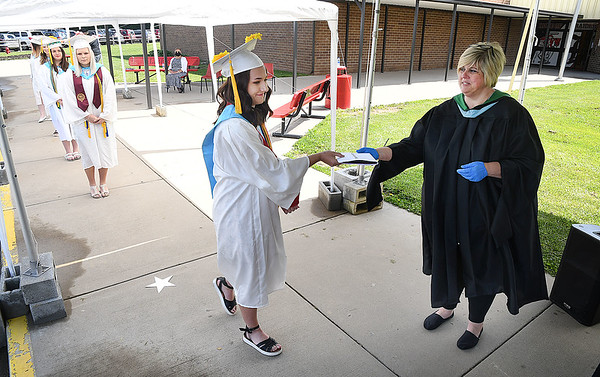Principal Lori Knight, of Liberty, right, hands Morgan Marty, her diploma in front of the High School Friday morning. Parents stayed in their vehicles and drove their graduates up to a designated area where they were able to get out in groups of 10 to control the setting of no more than 25 individuals gathering at once. Parents were able to hear speeches through their radio by tuning into 107.7 The River.<br /> (Rick Barbero/The Register-Herald)