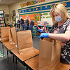 Katie Cooper, teacher at Crescent Elementary School, cleans out her students desks and bags up materials belonging to them to pick up at a later date. Students normally help, but could not because of COVID-19.<br /> (Rick Barbero/The Register-Herald)