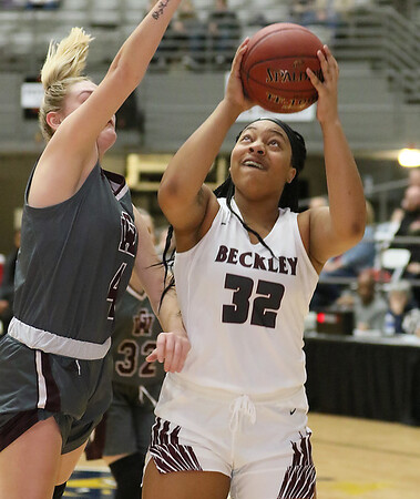 (Brad Davis/The Register-Herald) Woodrow Wilson's Jamara Walton drives to the basket as George Washington's Lauren Harrison defends during the final night of Big Atlantic Classic action Saturday at the Beckley-Raleigh County Convention Center.
