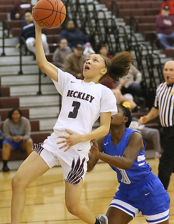 (Brad Davis/The Register-Herald) Woodrow Wilson's Keanti Thompson sails in for a layup off a partial breakaway as Capital's Natalyia Sayles is late to catch her Wednesday night in Beckley.
