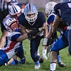 Midland Trail's Tyler Brasse gets a hand on the Meadow Bridge ball carrier. Chad Foreman for the Register-Herald.