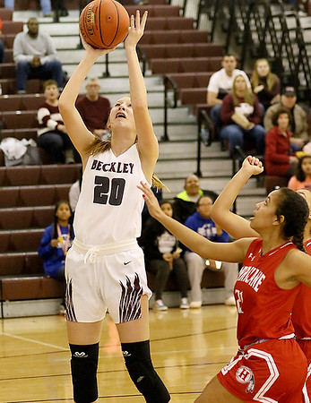 (Brad Davis/The Register-Herald) Woodrow Wilson's Camille Fenton drives and scores as Hurricane's Maggie Oduor defends Thursday night in Beckley.
