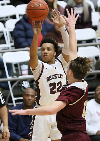(Brad Davis/The Register-Herald) Woodrow Wilson's Richard Law shoots from three-point range as George Washington's Evan Hughes defends Friday night at the Beckley-Raleigh County Convention Center.
