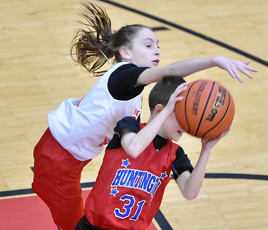 (Brad Davis/The Register-Herald) Beckley YMCA's Lacey Goodson tries to bat a rebound away from Huntington's Brayden McRussell during 5th Grade Roundball Classic action Saturday afternoon at the YMCA of Southern West Virginia. Huntington won the game.