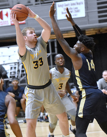 (Brad Davis/The Register-Herald) WVU Tech's Brent Daniels turns and shoots in the paint as Bluefield State's Alex Nunnally defends Saturday afternoon at the Beckley-Raleigh County Convention Center.