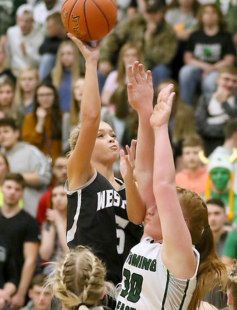 (Brad Davis/The Register-Herald) Westside's Riana Kenneda drives and shoots short range as Wyoming East's Sarah Saunders defends Wednesday night in New Richmond.
