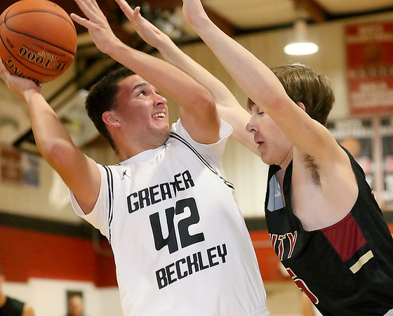 (Brad Davis/The Register-Herald) Greater Beckley's Ezra Drumheller drives to the basket as Trinity's Noah Kurilko defends Saturday night in prosperity.