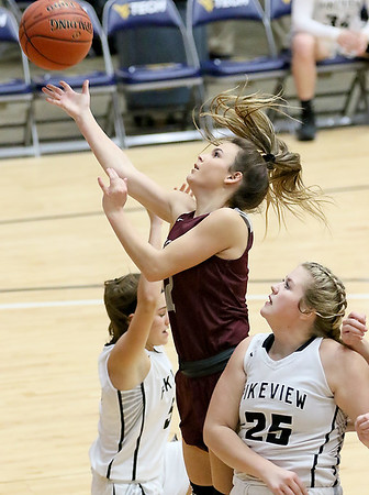 (Brad Davis/The Register-Herald) Woodrow Wilson's Cloey Frantz drives and scores as PikeView's Anyah Brown (#25) defends during the New River Community and Technical College Shootout Saturday at the Beckley-Raleigh County Convention Center.