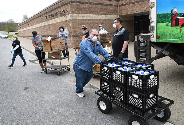 School employees and volunteers preparing to hand out meals at Westside High School for students in Wyoming County because of the coronavirus crisis.<br /> (Rick Barbero/The Register-Herald)