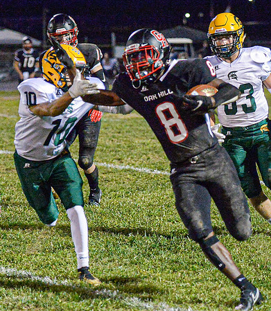 Greenbrier East's Trey Pondexter attempts to bring down Oak Hill's Leonard Farrow picks up yards during Friday evening action in Oak Hill. F. Brian Ferguson
