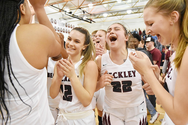 Members of the Woodrow Wilson Girls Basketball Team including Cloey Frantz, (12) and Sierra Conley (22) celebrate their Class AAA, Region Conference Final win over George Washington in Beckley on Tuesday. (Chris Jackson/The Register-Herald)