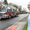 Tammy Evans, of Beckley, in front of her house on corner of, Park Ave. and Third Ave., watches a fire truck passes her home with a parade of cars not far behiind displaying signs celebrating one year anniversary of her daughter, Shannon Barbero, of Prosperity, donating half her liver to save her mothers life. Evans, who suffered from NASH, nonalcoholic steatohepatitis, stood her distance because of COVID-19, was surprised with a parade of 14 cars displaying messages and the sirens of two fire trucks. <br /> (Rick Barbero/The Register-Herald)