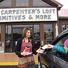 Paula Mullins, owner of Carpenter's Loft in Beckley, left, displaying some of her products to Ashlyn Perkins, of Beckley, in her parking lot. Her business is classified as non-essential because of COVID-19 and she now operates by receiving, Facebook, phone and curbside orders.<br /> (Rick Barbero/The Register-Herald)