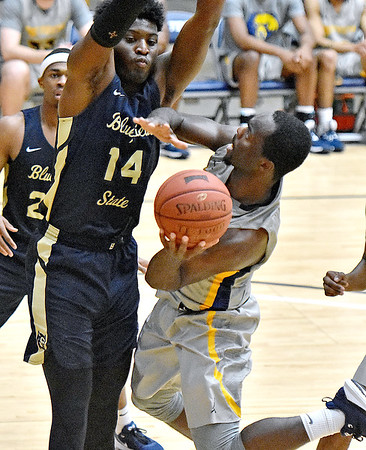 (Brad Davis/The Register-Herald) WVU Tech's Junior Arrey drives and scores as Bluefield State's Alex Nunnally defends Saturday afternoon at the Beckley-Raleigh County Convention Center.