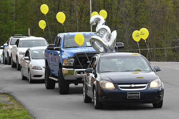 Vehicles filled with family members watch student receive their diploma at Shady Spring High School. Due to the COVID-19 global pandemic, students at Shady Spring High School were not able to take part in the traditional graduation ceremony like students in the past, but their administration made accommodations so their parents and family members could watch them walk across the stage, receive their diplomas, and turn their tassels Friday evening in front of the school.<br /> (Rick Barbero/The Register-Herald)