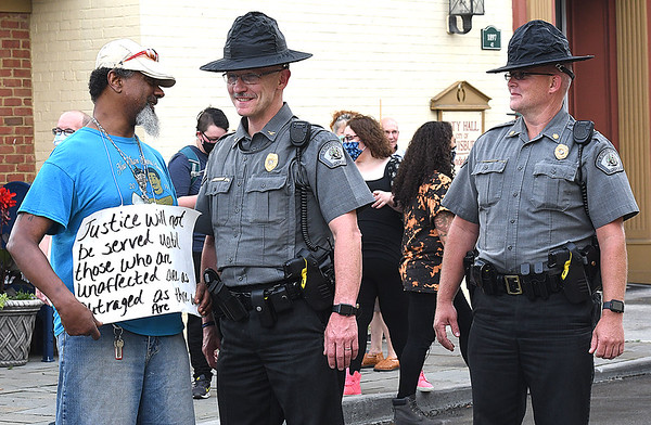 Tony Baxter, of Lewisburg, speak with Lewisburg City Police ocfficers during a Protest against racism and police brutality Thursday evening on Washington Street in Lewisburg.<br /> (Rick Barbero/The Register-Herald)