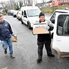 John Hicks and Darrly Scott, Raleigh County bus drivers, hand out the last meal packets for students at Stratton Elementary School Wednesday morning. Cars were backed up on South Fayette Strret waiting and many didn't receive meals because they ran out.<br /> (Rick Barbero/The Register-Herald)