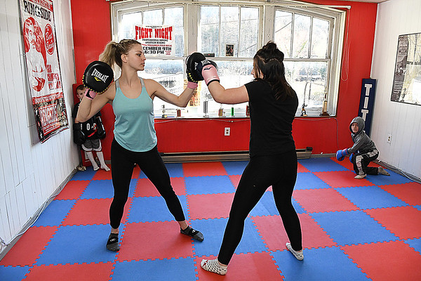 Hope McNeely, owner of A-Train Boxing & Fitness Studio in Mullens, left, training Rileigh Mullins in her gym.<br /> (Rick Barbero/The Register-Herald)