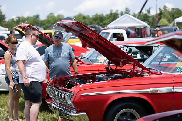 Brothers James and John Given and Johns wife Christina admiring David Bleigh's Red 1964 Plymoth at the Friends of Charity Auto Fair<br /> Tina Laney/for The Register-Herald