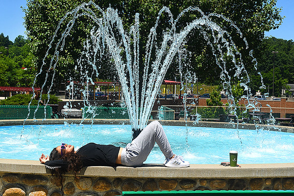 Bernadette Hernandez, who recently moved to Beckley from Destin Florida, enjoying the weather by resting on the ledge of the fountain in Word Park on Neville Street in Beckley Wednesday afternoon.<br /> (Rick Barbero/The Register-Herald)