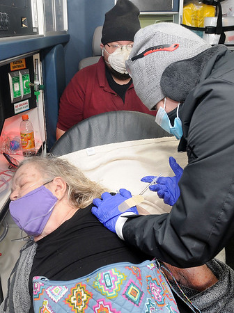Dixie Harvey, of Oak Hill, gets a vaccine in the back of an ambulance from Keely Tucker, from the Academy of Careers and Technology. Jon C. Hancock/for The Register-Herald