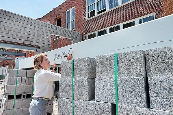 Sen. Shelley Capito signs a beam on the new Schoolhouse Hotel during a tour of downtown White Sulphur Springs Friday.  Jenny Harnish for the Register-Herald