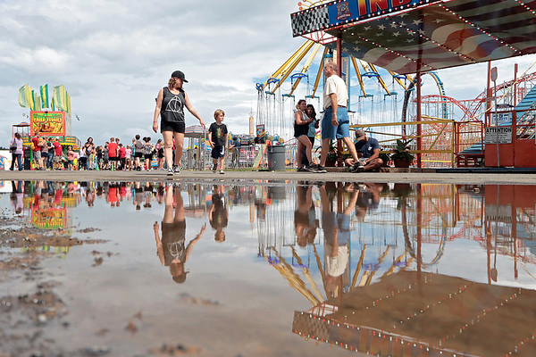 Fairgoers are reflected in a puddle at the State Fair of West Virginia in Fairlea Monday. Rain is in the forecast for most of the week. Jenny Harnish/The Register-Herald