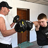 Butch McNeely, left, works with Matthew Campbell at A-Train Boxing & Fitness Studio in Mullens. Butch is the father of Hope McNeely, owner of the gym. (Rick Barbero/The Register-Herald)