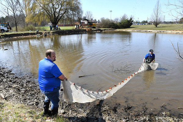 Dennis Burns, left, and Kenny Maiolo, both with WV Conservation Agency, drag a net in the pond in front of Woodrow Wilson High catching fish as the pond gets drained so it can be turned into a wetland.<br /> (Rick Barbero/The Register-Herald)