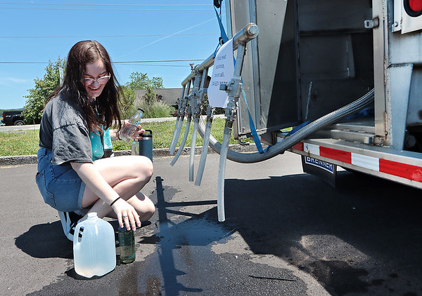 Meg LaFollette fills up water at a self-serve water tanker for potable water in Lewisburg Thursday. The City of Lewisburg issued a boil water advisory Wednesday because of high turbidity levels due to excess rain and storms in the region. Jenny Harnish for the Register-Herald
