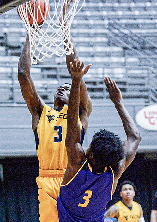 WVU Tech's Ashton Parker drives for the rim as Carlow University's Marcus Millien defends during Friday evening action in Beckley. F. Brian Ferguson