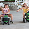 Best friends Calleigh Rudd, left, and Grace Brown race tractors at the Farm to Food Pavilion at the State Fair of West Virginia Monday. Jenny Harnish/The Register-Herald