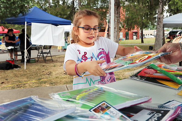 Raylin Stidom, 5, receives free school supplies from Read A Loud WV at the Alderson Community Market Tuesday. Jenny Harnish/The Register-Herald