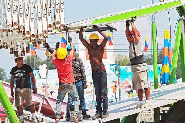 Workers put together a ride at the State Fair of West Virginia Monday.  Jenny Harnish/The Register-Herald