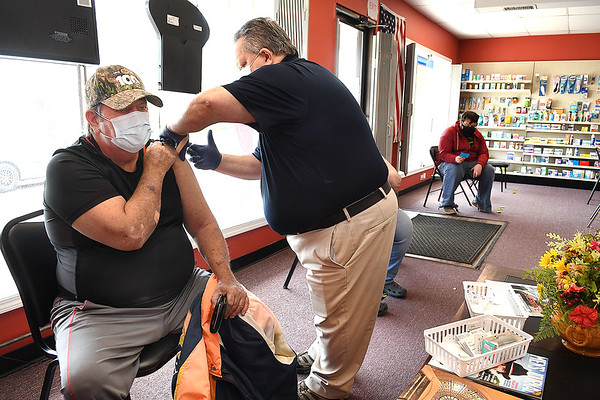Gary Cunningham, pharmacist of Bypass Pharmacy on Eisenhower Drive in Beckley, gives a COVID-19 vaccinations to Lawerence Rakes, of Sophia.<br /> (Rick Barbero/The Register-Herald)