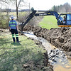 Raleigh County Board of Education employees are digging a trench to drain the water in the pond in front of Woodrow Wilson High. They are draining the pond so it can be turned into a wetland.<br /> (Rick Barbero/The Register-Herald)