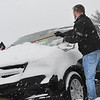 Brandon Williams, of Beckley, cleans snow off a car in the parking lot of Sheet on Auto Plaza Drive in Beckley Thursday morning.<br /> (Rick Barbero/The Register-Herald)