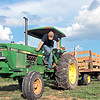 Alex Hanna jumps off the tractor at The Hanna Farmstead in Maxwelton Saturday. Alex Hanna and Jade Napier are having games, barrel rides, wagon rides, roasted corn and sunflowers at their agro-tourism farm on weekends through October 31. Jenny Harnish/The Register-Herald
