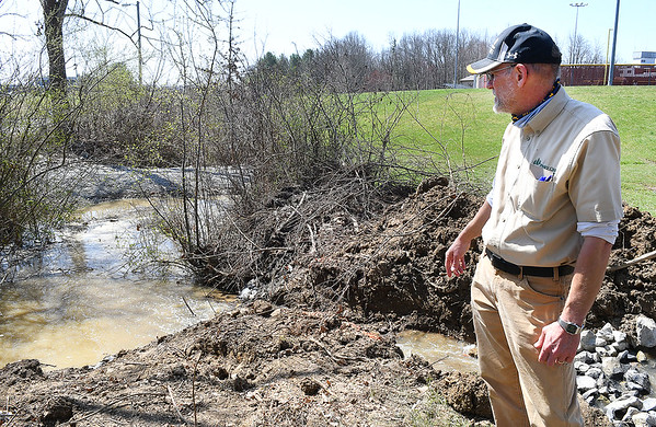 Jim Fedders, director of Piney Creek Watershed Association, looks over a rock creek dam that helps catch sediment as they drain the water of the pond in front of Woodrow Wilson High. They are draining the pond so it can be turned into a wetland.<br /> (Rick Barbero/The Register-Herald)