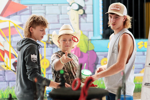 From left, Alex Farley, Kennison Adkins and Austin Farley play the ring toss at the State Fair of West Virginia Wednesday. Jenny Harnish/The Register-Herald