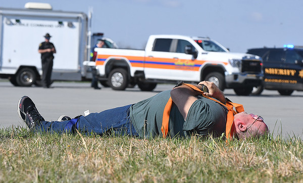 Passenger from a simulator airplane lays hurt on the ground during a mock disaster plane wreck held at the Raleigh County Memorial Airport in Beaver Tuesday morning. This was a training excerise that's conducted every three years for airport employees to be FAA certifield.<br /> (Rick Barbero/The Register-Herald)