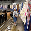 Cheryl Eccles Clark, member of the Appalachian Treasure Quilt Show, arranges quilts around the arena of the Beckley-Raleigh County Convention Center preparing for the opening of the Appalachian Makers Market that wil be held with fifty vendors on Friday 9 am to 7 p.m. and Saturday 9 am to 5 p.m. Participants entered 57 quilts for competition competing in fifteen categories that was judged Thursday. The People Choice Award will be announce at the end of the show on Saturday.<br /> (Rick Barbero/The Register-Herald)