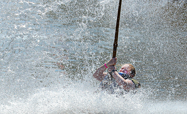 Girl Scout Madeleine Drake-Metzger rides a zip lines into the lake at Ace Adventure Resort in Oak Hill on Monday morning. Hundreds of girl scouts from around the country converged on the resort for a week of outdoor activities, F. Brian Ferguson/Register-Herald