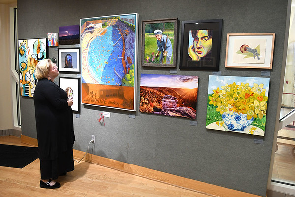 Mandy Lash, gallery director Tamarack, looks over the Best of West Virginia 13th Annual Open Juried exhibit displayed in the gallery at Tamarack. Ninety five artist from all over the state displayed 125 pieces of artwork that was juried by Elaine Gustafson and Ron Donoughe. Best of show was awarded to Coal Camp, by Patty Wolford, second place- Looking Back, by Richard Shrewsberry and third place- Swim in Pure Drinking Water, by Michael Teel. People Choice will be awared when the show closes out on August 1.<br /> (Rick Barbero/The Register-Herald)